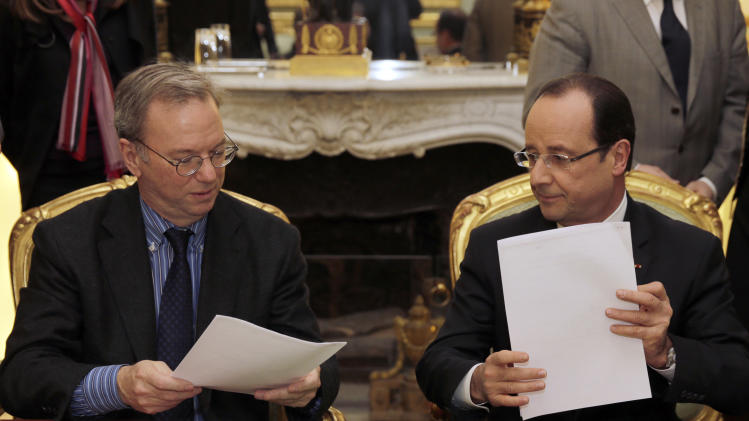 FILE - This Friday, Feb. 1, 2013, file photo shows Google CEO, Eric Schmidt, left, and French President Francois Hollande signing an agreement at the Elysee Palace in Paris. Google's new privacy policy is under attack from regulators in its largest European markets, who on Tuesday, April 2, 2013 brought legal action to try and force the company to overhaul practices they say let it create a data goldmine at the expense of unwitting users. (AP Photo/Philippe Wojazer, Pool-File)