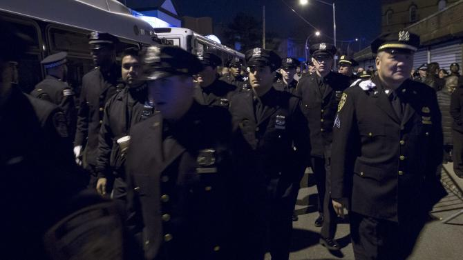 Police officers wait in line after sunset to attend the wake of slain NYPD officer Rafael Ramos at Christ Tabernacle Church in the Queens borough of New York