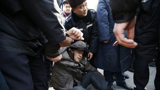 Family member of a passenger onboard the missing Malaysia Airlines flight MH370, is stopped by policemen as he tries to approach the Malaysian Embassy during a protest demanding the Malaysian government to keep searching the missing flight, in Beijing