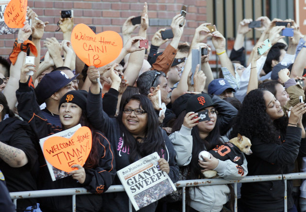 San Francisco Giants fans cheer as the team buses arrive outside of AT&T Park in San Francisco, Monday, Oct. 29, 2012. The Giants defeated the Detroit Tigers to win baseball's World Series. (AP Photo/Jeff Chiu)