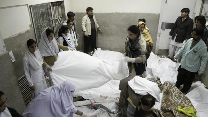 Pakistani medics and volunteers cover the lifeless bodies of a bomb blast victims, at a hospital in Quetta, Pakistan, Saturday, Feb. 16, 2013. A bomb ripped through a crowded vegetable market in a mostly Shiite neighborhood in a southern Pakistani city Saturday, killing scores of people in a horrific attack on the country's minority Muslim sect. (AP Photo/Arshad Butt)
