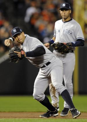 New York Yankees third baseman Alex Rodriguez, front, fields a ground ball by Baltimore Orioles' Matt Wieters in front of shortstop Derek Jeter in the second inning of Game 2 of the American League division baseball series on Monday, Oct. 8, 2012, in Baltimore. (AP Photo/Nick Wass)