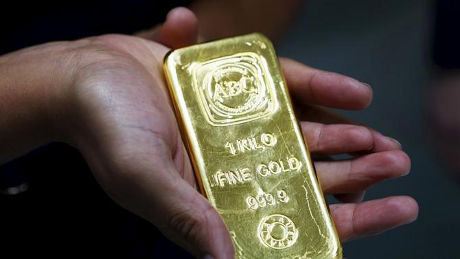 File picture of a woman holding a one-kilogram gold bar at the headquarters of the Australian Bullion Company (ABC) in Sydney