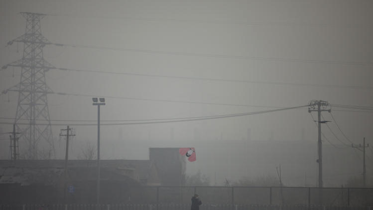 A man flies a kite near electricity pylons on a hazy day in Beijing Saturday, Jan. 12, 2013. Air pollution levels in China's notoriously dirty capital were at dangerous levels Saturday, with cloudy skies blocking out visibility and warnings issued for people to remain indoors. (AP Photo/Alexander F. Yuan)
