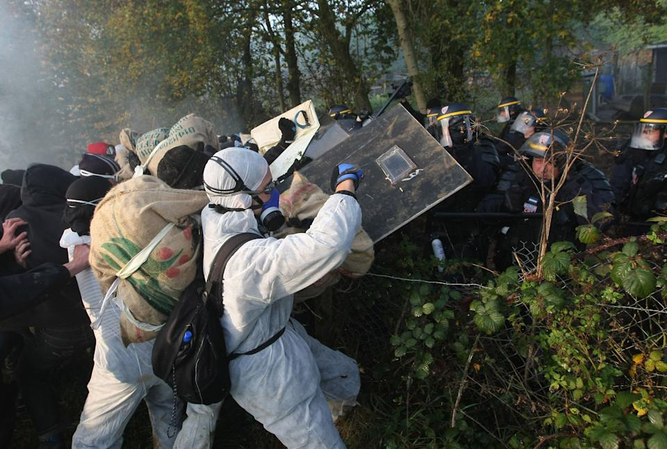 Activists clash with riot police officers early Wednesday, Nov. 23, 2011,  in Lieusaint, Normandy, France, as they try to block a rail line to stop a train loaded with nuclear waste and heading to Gorleben in Germany. (AP Photo/David Vincent)