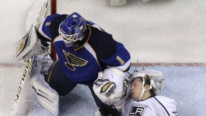 Los Angeles Kings' Tyler Toffoli, right, falls as St. Louis Blues goalie Brian Elliott, top, and Blues' Chris Stewart (25) defend during the first period in Game 5 of a first-round NHL hockey Stanley Cup playoff series, Wednesday, May 8, 2013, in St. Louis. (AP Photo/Jeff Roberson)