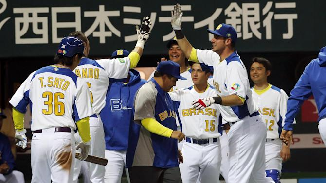 Brazil's center fielder Paulo Orlando, second from left, celebrates with teammate Alan Fanhoni, right, after scoring a run against Japan in the fifth inning of their World Baseball Classic first round game in Fukuoka, Japan, Saturday, March 2, 2013. (AP Photo/Koji Sasahara)