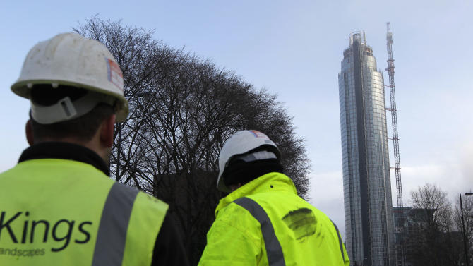 People look at the St. George Wharf Tower with part of the construction crane missing after a helicopter crashed into it, in central London, Wednesday Jan. 16, 2013. Police say two people were killed when a helicopter crashed Wednesday during rush hour in central London after apparently hitting a construction crane on top of a building. (AP Photo/Sang Tan)