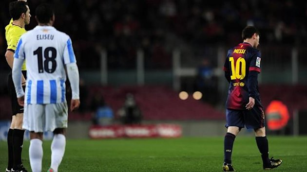 The referee shows a yellow card to Barcelona's Lionel Messi during the Copa del Rey quarter-final against Malaga (AFP)