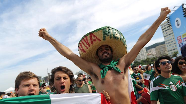 Mexico soccer fans, wearing their team's national colors, pose for the picture before watching their team's World Cup round of 16 match against Netherlands on a live telecast inside the FIFA Fan Fest area on Copacabana beach in Rio de Janeiro, Brazil, Sunday, June 29, 2014. (AP Photo/Leo Correa)