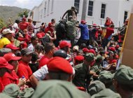 Soldiers try to help maintain order among the crowd of supporters of Venezuela's late President Hugo Chavez, as many collapsed while waiting to view his body in state at the Military Academy in Caracas, March 7, 2013. REUTERS/Tomas Bravo
