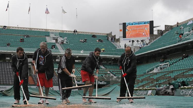 Stadium employees clear water from center court as matches were delayed because of the rain at the French Open tennis tournament, at Roland Garros stadium in Paris, Tuesday, May 28, 2013. (AP Photo/Michel Spingler)