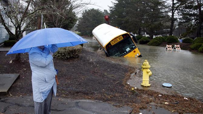 A submerge school bus lays on its side as Diane Garibaldi looks on Thursday, Jan. 19, 2012, in Salem, Ore. Up to 10 inches of rain fell on parts of the Oregon Coast Range in a 36-hour period, and more rain and flooding is on the way, the National Weather Service said.  (AP Photo/Rick Bowmer)
