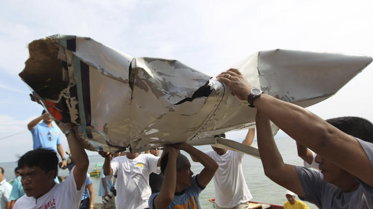 In this photo released by the Malacanang Photo Bureau, men carry parts of a crashed plane carrying Philippine Interior Secretary Jesse Robredo in Masbate city, Masbate province, central Philippines, Sunday, Aug. 19, 2012. About 300 rescuers were searching Sunday for Robredo and his two pilots after their small plane crashed into the sea while attempting an emergency landing on Saturday. (AP Photo/Malacanang Photo Bureau, Jay Morales) NO SALES