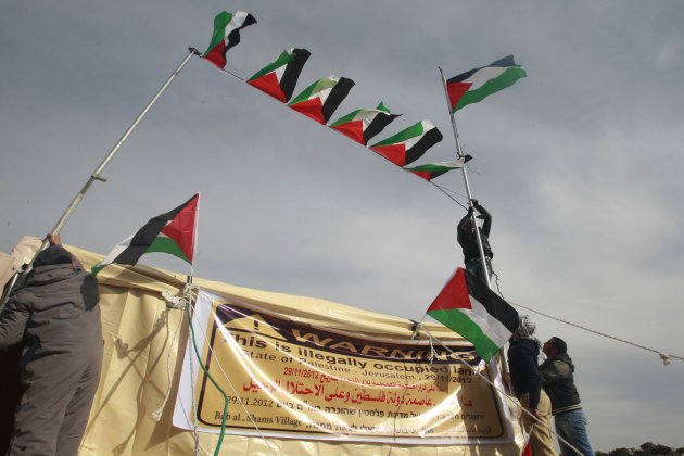 Palestinian activists place Palestinian flags in the new 'outpost ' of Bab al-Shams (Gate of the Sun) in an area known as E1, near Jerusalem, Saturday, Jan 12, 2013. Palestinian activists pitched tents in the West Bank on Friday to protest Israeli plans to build a large Jewish settlement on a key route through the territory. The E-1 settlement would block east Jerusalem from its West Bank hinterland — both territories captured by Israel during the 1967 Mideast war. (AP Photo/Nasser Shiyoukhi)