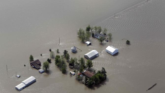 FILE - In this May 3, 2011, file photo a farm is surrounded by floodwater in Mississippi County, Mo., after the Army Corps of Engineers' blew a two-mile hole into the Birds Point levee and flooded 130,000 acres of farmland.   Utah and Missouri stand to receive more than one-third of $308 million in federal disaster aid announced Wednesday, Jan. 18, 2012,  by Agriculture Secretary Tom Vilsack in response to an unusually intense year of tornadoes, floods and forest fires across the nation.  (AP Photo/Jeff Roberson, File)