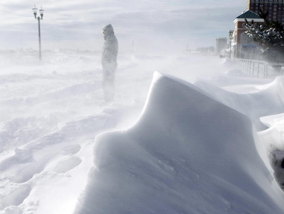 A man turns his back as strong winds blow snow across The Boardwalk Monday, Dec. 27, 2010, in Atlantic City, N.J. (AP Photo/Mel Evans)