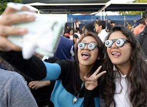 Children take pictures during an attempt to break a world record for largest gathering of people wearing googly eye glasses at a Halloween party in Los Angeles
