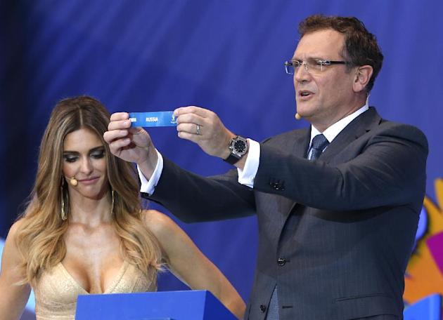 FIFA Secretary General Jerome Valcke shows the ticket of Russia during the draw ceremony for the 2014 soccer World Cup in Costa do Sauipe near Salvador, Brazil, Friday, Dec. 6, 2013