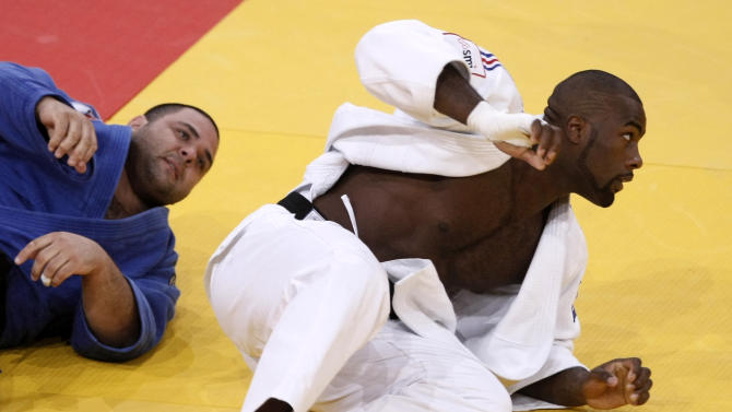 Teddy Riner of France, blue jersey, fights with Daniel Hernandez of Brazil during their men's over 100 kg category elimination round at the World Judo Championships in Paris Saturday, Aug. 27, 2011. (AP Photo/Michel Spingler)