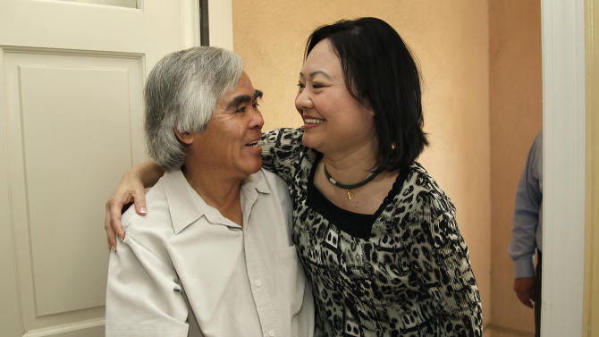 FILE- In this June 2, 2012, file photo, Phan Thi Kim Phuc, right, hugs Associated Press staff photographer Nick Ut during a reunion in Buena Park, Calif. It only took a second for Ut to snap the iconic black-and-white image of Phan Thi Kim Phuc after a napalm attack in 1972, but it communicated the horrors of the Vietnam War in a way words could never describe, helping to end one of America's darkest eras. (AP Photo/Jae C. Hong, File)