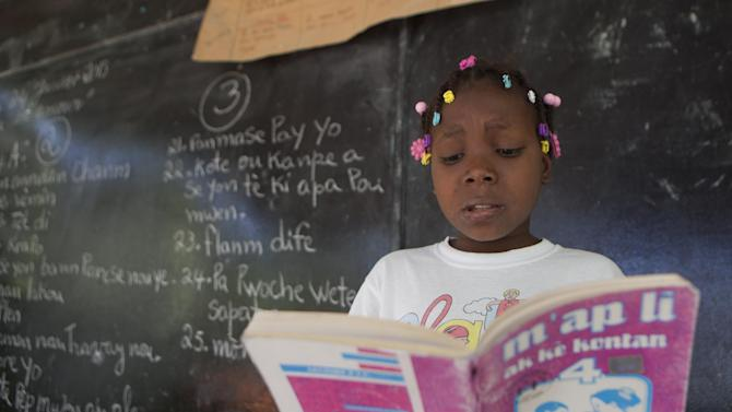 "In this Jan. 24, 2013 photo, Cassandra Meon, 11, reads a textbook before her classmates that reads in Creole ""I'm Reading With a Happy Heart"" as she attends her Creole language class at the Louverture Cleary School, which also teaches French, English and Spanish, in Croix-des-Bouquets, Haiti. Creole advocates say that there's no shortage of Creole-language books and point to publishing houses such as Educa Vision, Inc. in Florida, which produce such materials. But they acknowledge that shipping the materials to Haiti is expensive and goods are often held up in customs. (AP Photo/Dieu Nalio Chery)"
