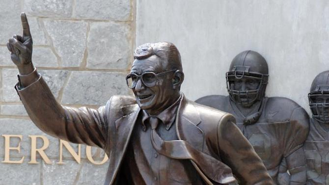 FILE - A statue of former Penn State University head football coach Joe Paterno stands outside Beaver Stadium on in this July 12, 2012 file photo. Police and construction workers have barricaded both sides of street and the sidewalks near the Joe Paterno statue at Penn State University. A chain-link fence has been erected around the perimeter surrounding the statue.  (AP Photo/Gene J. Puskar, File)