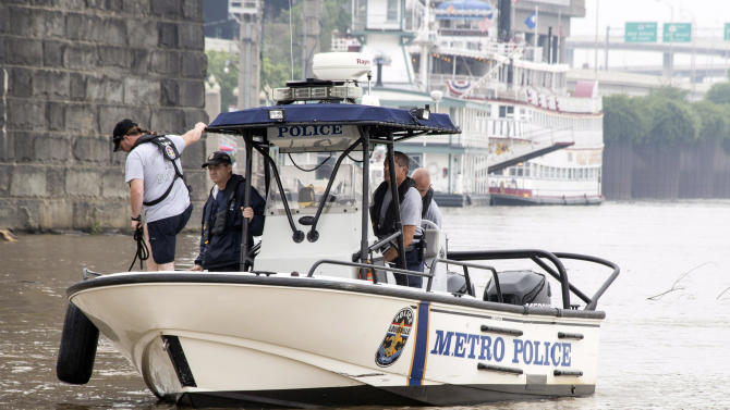 Authorities stand on a Louisville Metro Police Department boat, Sunday, July 5, 2015, on the Ohio River in Louisville, Ky. Authorities say at least three people were killed and multiple people are missing after a boat they were riding in hit the Clark Memorial Bridge and capsized in to the Ohio River on Saturday night. (Marty Pearl/The Courier-Journal via AP)