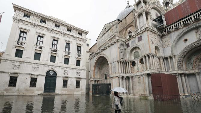 A woman walks through the flooded St. Mark's Square during a period of seasonal high water and on the first day of carnival, in Venice