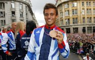 British bronze medal winning diver Tom Daley poses on his float during a parade celebrating Britain&#39;s athletes who competed in the London 2012 Olympic and Paralympic Games in central London. Huge crowds cheered Britain&#39;s Olympic and Paraylmpic athletes during a victory parade to Buckingham Palace amid hopes that the golden sporting summer will give the country a long-term boost
