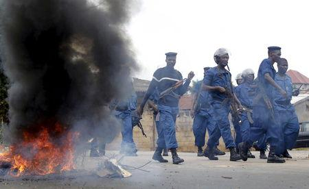 Riot policemen walk past a barricade during street protests in Bujumbura