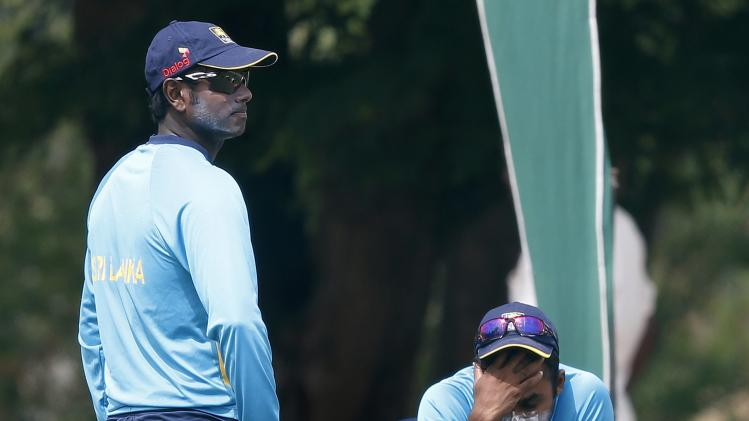 Sri Lanka's captain Mathews looks on as his teammate Jayawardene rests during a practice session ahead of their second ODI cricket match against Pakistan in Hambantota