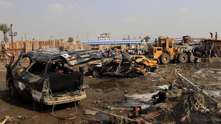 People inspect the scene of a car bomb attack in Baghdad's northern Kazimyah neighborhood, Friday, Feb. 8, 2013. Car bombs struck two outdoor markets in Shiite areas of Iraq on Friday killing and wounded scores of people, police said. (AP Photo/ Karim Kadim)