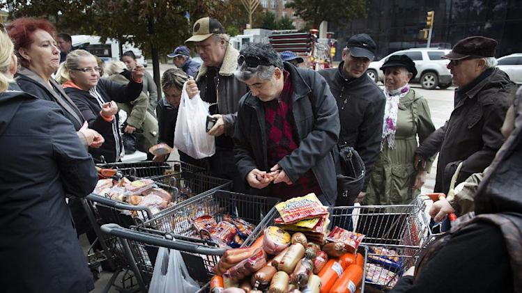 A customer browses food piled into shopping carts on Brighton Beach Avenue, Wednesday, Oct. 31, 2012, in the Brooklyn borough of New York. People in the coastal corridor battered by superstorm Sandy took the first cautious steps Wednesday to reclaim routines upended by the disaster, even as rescuers combed neighborhoods strewn with debris and scarred by floods and fire. (AP Photo/ John Minchillo)