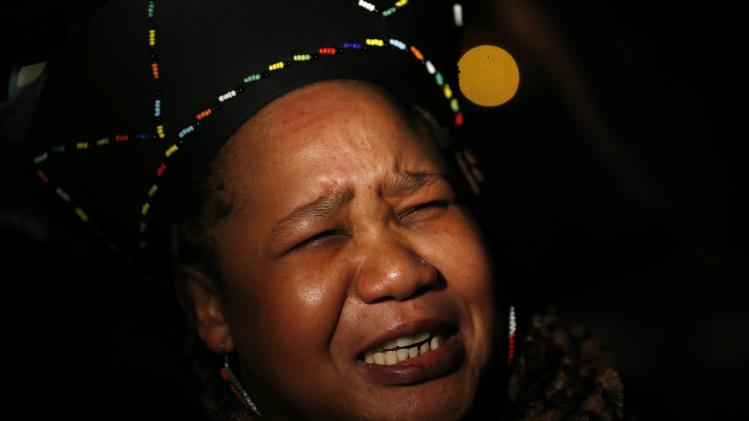 Busi Mhlanga reacts at a gathering in memory of Nelson Mandela outside the South African High Commission in London