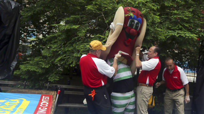 Nathan's employees help the mascot get into his costume before the official weigh-in