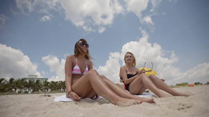 "In this Wednesday, May 9, 2012 photo, Morgan Weese, 23, left, and Brittany Locke, from Tempe, Ariz. sun bathe in Miami Beach, Fla. during their vacation. Weese said she used to ""obsessed"" with tanning during high school, but now knows the dangers associated with tanning too much - including skin cancer. (AP Photo/J Pat Carter)"