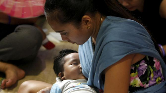 A mother breastfeeds her child while texting in Mandaluyong City