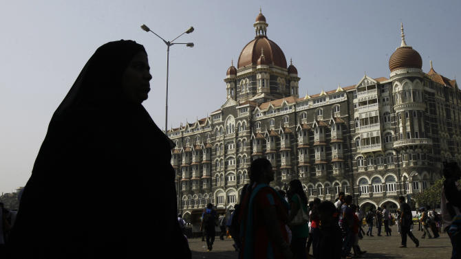 People walk past the Taj Mahal hotel, one of the targets of the 2008 terror attacks in Mumbai, India, Wednesday, Nov. 21, 2012. India executed the lone surviving Pakistani gunman from the 2008 terror attack on Mumbai early Wednesday, providing Indians much-needed closure over the three-day rampage that shook the nation's core and deepened enmity with neighbor Pakistan. (AP Photo/Rafiq Maqbool)