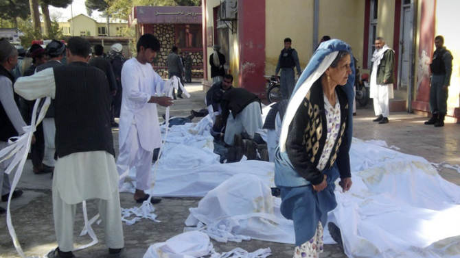 Bodies of suicide attack victims are covered in white cloth in the courtyard of a hospital in Maymana, Faryab province, northwest of Kabul, Afghanistan, Friday, Oct. 26, 2012. A suicide bomber blew himself up outside a mosque in northern Afghanistan on Friday, killing dozens of people and wounding scores, government and hospital officials said. (AP Photo/Qawtbuddin Khan)