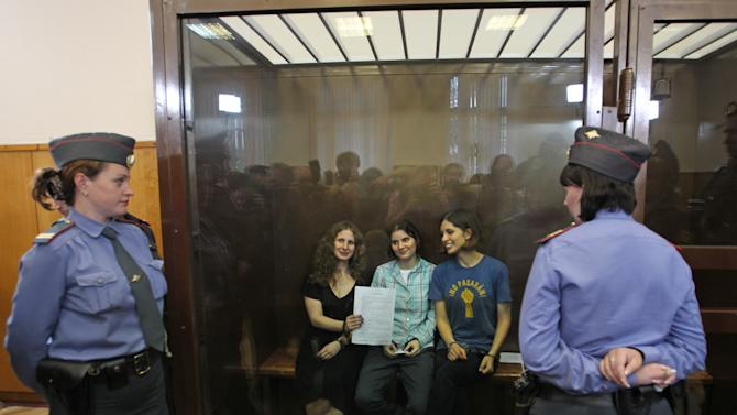 Feminist punk group Pussy Riot members, from left, Maria Alekhina, Yekaterina Samutsevich, and Nadezhda Tolokonnikova show the court's verdict as they sit in a glass cage at a court room in Moscow, Russia Friday, Aug 17, 2012. A judge found three members of the provocative punk band Pussy Riot guilty of hooliganism on Friday, in a case that has drawn widespread international condemnation as an emblem of Russia's intolerance of dissent. (AP Photo/Mikhail Metzel)