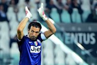 Juventus&#39; goalkeeper Gianluigi Buffon acknowledges the audience during the Serie A football match between Juventus and Chievo Verona at the Stadio delle Alpi in Turin, on September 22. Serie A champions Juventus pulled ahead of the rest of the pack with a 2-0 win over Chievo as their closest challengers slipped up on a dramatic fourth round of matches Sunday