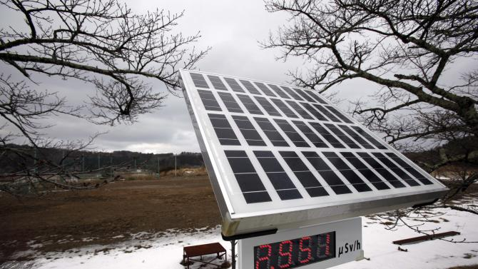 In this Sunday, March 3, 2013 photo, a solar-powered radiation meter indicates radiation levels beside the sports ground of a school in the abandoned town of litate, outside the exclusion zone surrounding the Fukushima Dai-ichi nuclear plant in Japan. Two years after the triple calamities of earthquake, tsunami and nuclear disaster ravaged Japan's northeastern Pacific coast, radioactive and chemical contamination remains a threat as clean-up projects face troubles with organized crime and mishandling. (AP Photo/Greg Baker)