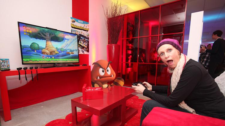 Actress Jane Lynch warms up and checks out Wii U at the Nintendo Lounge while playing New Super Mario Bros. U during a break from the Sundance Film Festival on Sunday, Jan. 20, 2013 in Park City, UT. (Photo by Donald Traill/Invision for Nintendo/AP Images)