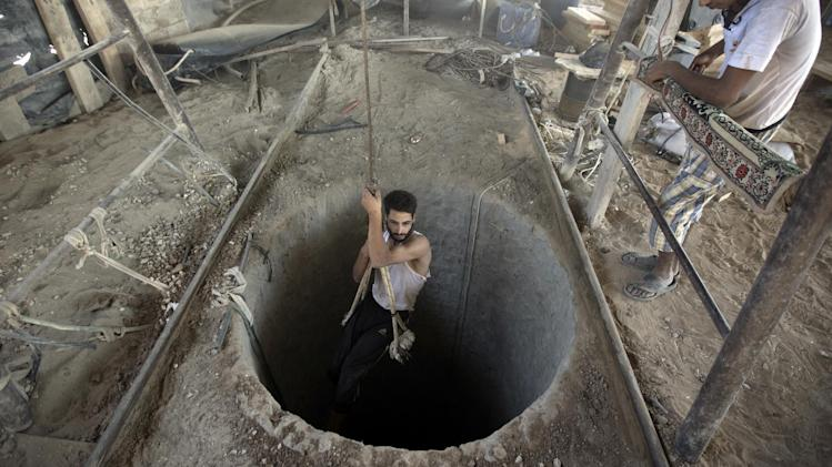A Palestinian man is lowered into a smuggling tunnel beneath the Gaza-Egypt border, in the southern Gaza Strip, on September 11, 2013