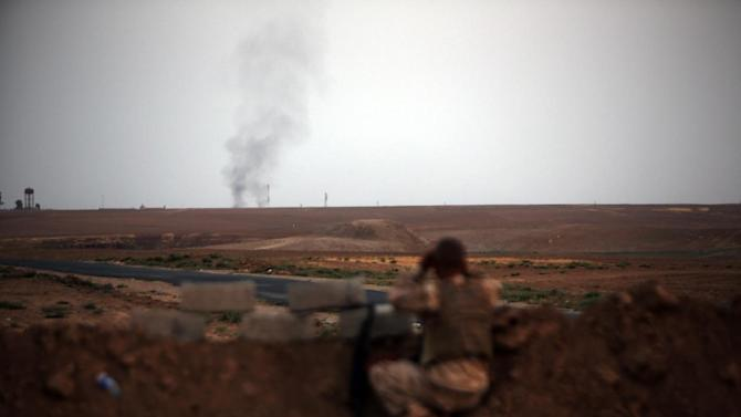 A Peshmerga fighter looks at smoke rising in the horizon on the front line of battles with Islamic State militants east of Mosul, on August 18, 2014