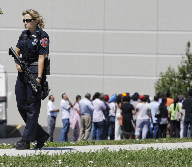 Police stand guard as bystanders watch at the scene of a shooting inside a Sikh temple in Oak Creek, Wis., Sunday, Aug. 5, 2012. Police and witnesses describe a chaotic situation with an unknown numbe