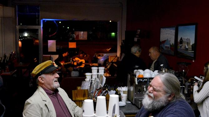 In this Nov. 8, 2012 photo, Jim Elder, left, laughs with shop owner Bryan Baine at Baine's Books in Appomattox, Va. In the heart of this historic village, townspeople gather for coffee and conversation in the Main Street institution and, every Thursday after sundown, an open mic night draws performers from near and far. (AP Photo/Pat Jarrett)