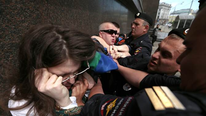 """Police detain a gay rights supporter, left, and an opponent, right, who scuffle during an unsanctioned gay rally near the City Hall in Moscow, Saturday, May 25, 2013. The Kremlin initiated a bill banning """"propaganda of homosexuality"""" and routinely banned gay rallies and parade.  Russian police say they detained at least 30 gay rights campaigners and their opponents at an unsanctioned rally in Moscow. (AP Photo/Ivan Sekretarev)"""