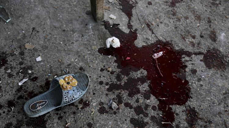 A sandal and a pool of blood remain at the site of an Israeli strike that hit a U.N. school in Beit Hanoun, in the northern Gaza Strip, Thursday, July 24, 2014. Israeli tank shells hit the compound, killing more than a dozen people and wounding dozens more who were seeking shelter from fierce clashes on the streets outside, Palestinian officials said, as Israel pressed forward with its 17-day war against the territory's Hamas rulers. (AP Photo/Adel Hana)